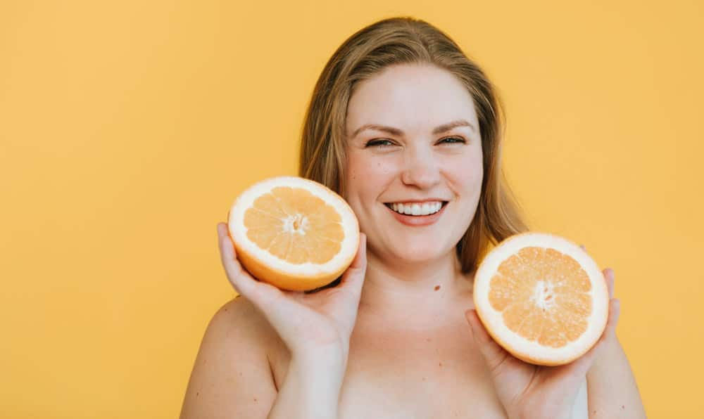 Positive thinking woman eating grapefruits