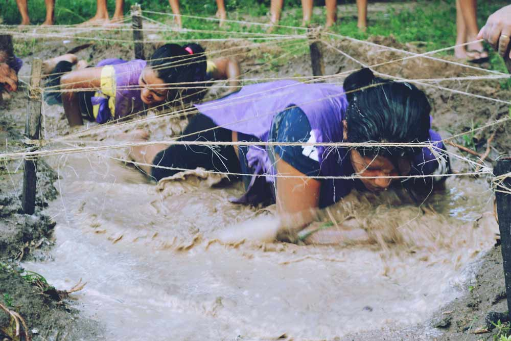 Woman taking on new challenge getting through the mud