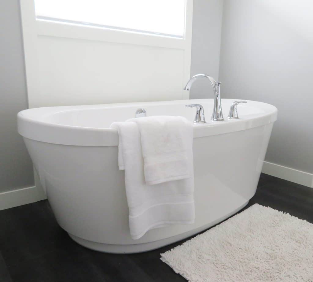 White Ceramic Bathtub Near Window.